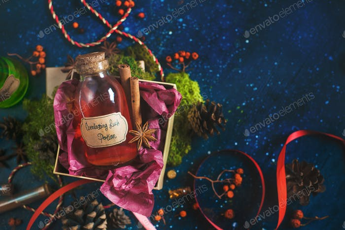 Present box with a bottle of Luck Potion. Magical still life with potion bottles, ingredients and