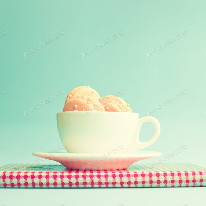Pink macaroons in a cup