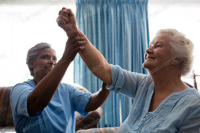 Nurse helping senior woman in flexing muscles