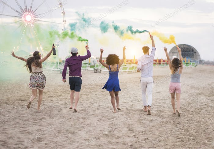 Young friends running with smoke bombs and champagne bottle at beach festival