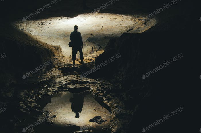 man exploring dark cave underground tunnel