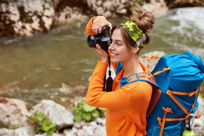 Mirthful female traveler takes photo on camera, focused into distance, wears headband, orange sweate