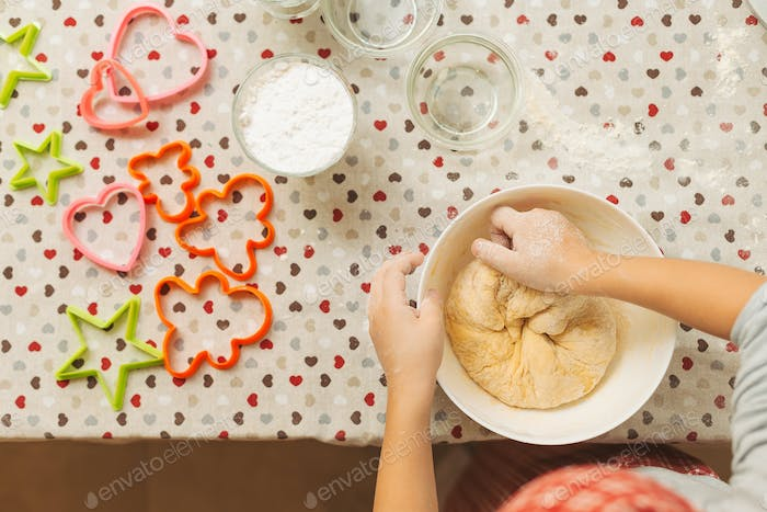 Child hands mixing dough for cookies