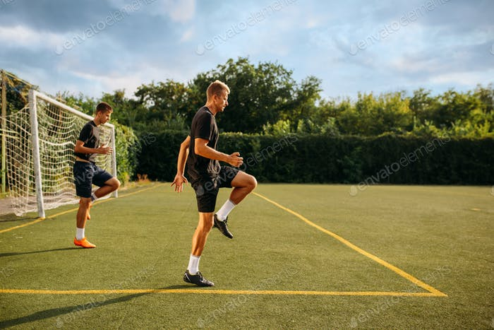 Two male soccer players training on the field