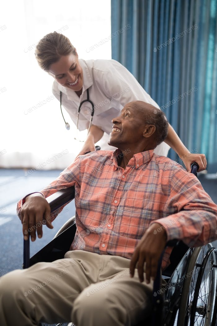 Smiling female doctor looking at disabled senior man sitting on wheelchair against window