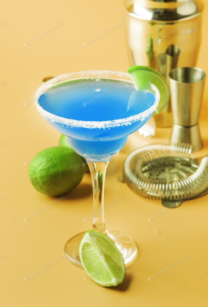 Blue margarita alcoholic cocktail with tequila, liqueur, lime juice, salt and ice