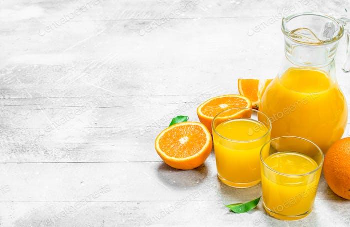Orange juice and fresh ripe oranges.