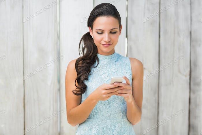 Morena elegante en el teléfono contra la valla de De madera blanqueada