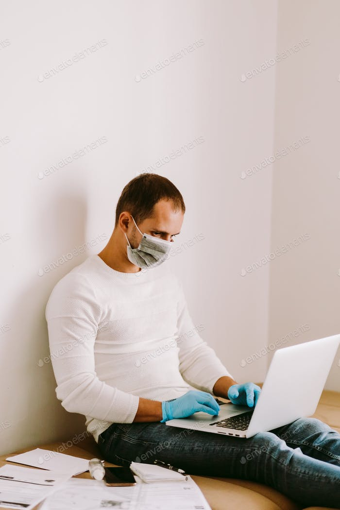 Mann, der zu Hause mit Laptop und Smartphone während der Quarantäne arbeitet