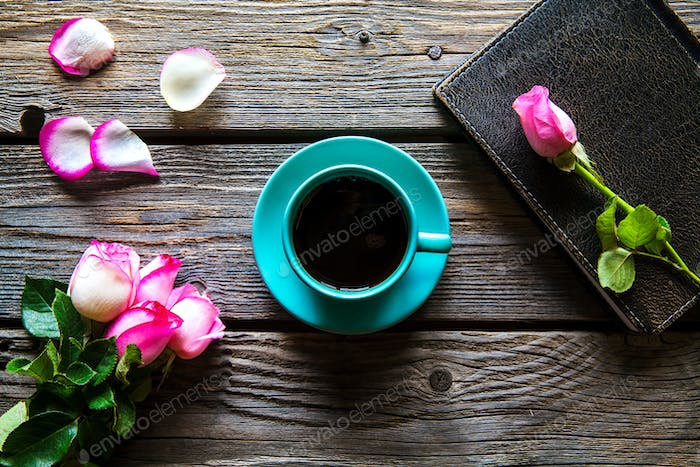 Fresh roses with diary and cup of coffee on wooden table, top view. flowers, hot drink