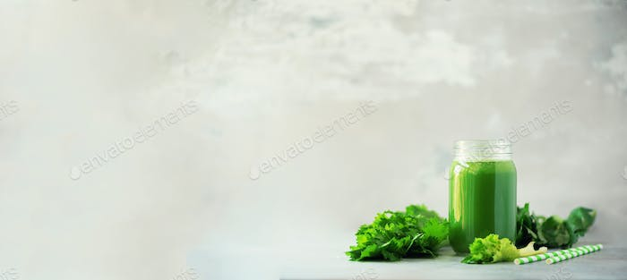 Bottle of green celery smoothie on grey concrete background. Banner with copy space. Square crop