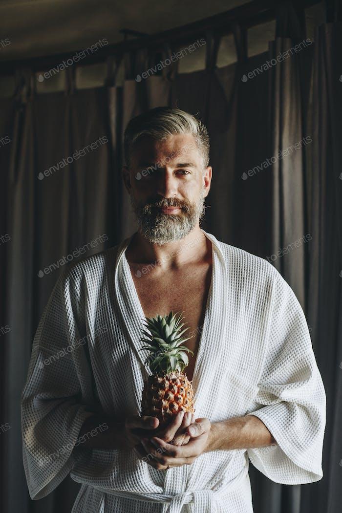 Man in a bathrobe holding a pineapple