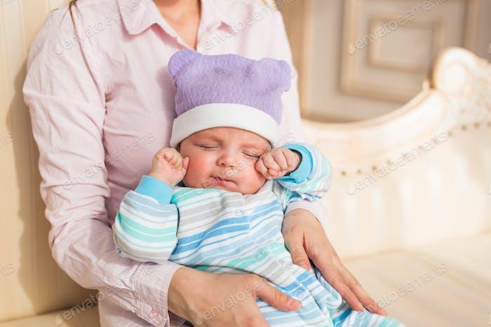 Tired newborn baby boy rubbing eyes