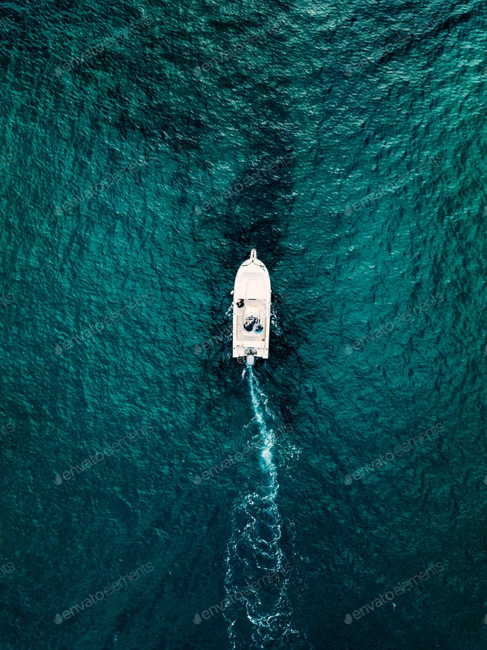 Aerial view of speed boat in motion in blue sea in Italy.