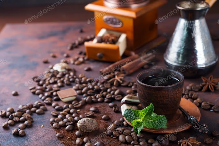 a cup of coffee, coffee beans and fresh mint leaves on a brown background. Copy space for you text