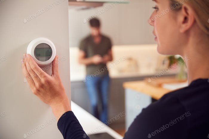 Close Up Of Woman Adjusting Wall Mounted Digital Central Heating Thermostat Control At Home