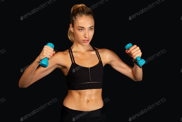 Determined Woman Exercising With Dumbbells, Studio Shot