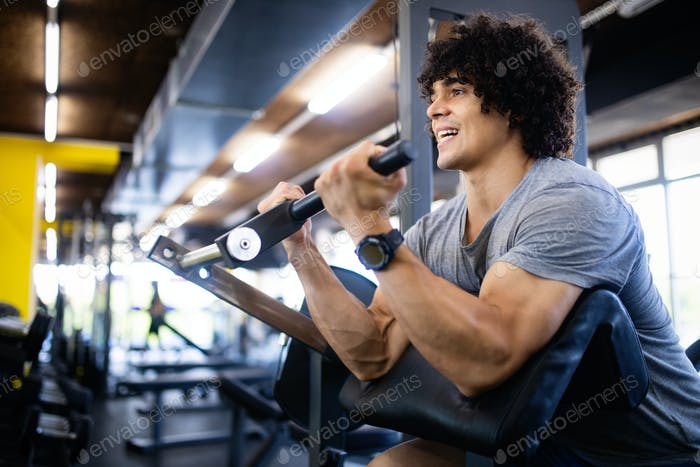Fit healthy handsome man exercising in modern gym