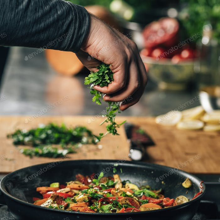 Hand Adding Parsley into Frying Pan with Vegetables