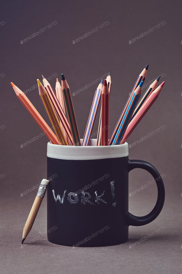 Close-up photo of a group multicolored pencils in black mug.
