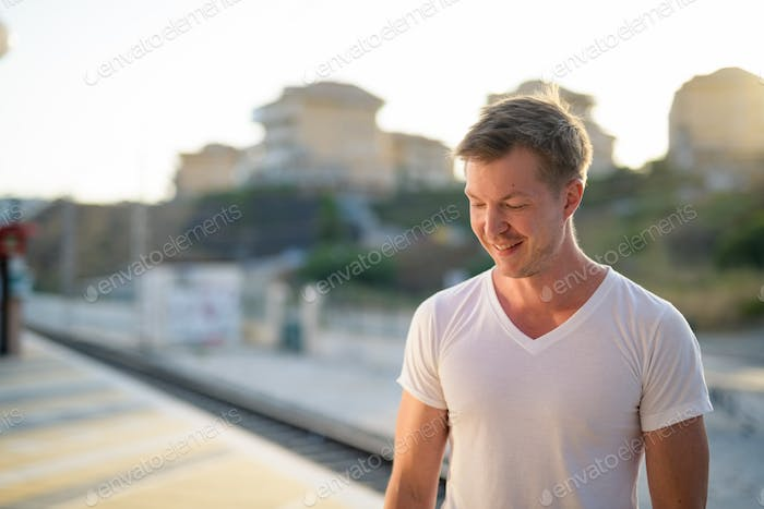 Young Handsome Tourist Man Smiling And Thinking At The Train Station