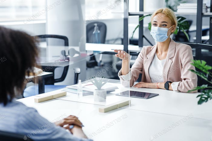 African american lady speaks to business woman in protective mask through glass partition in office