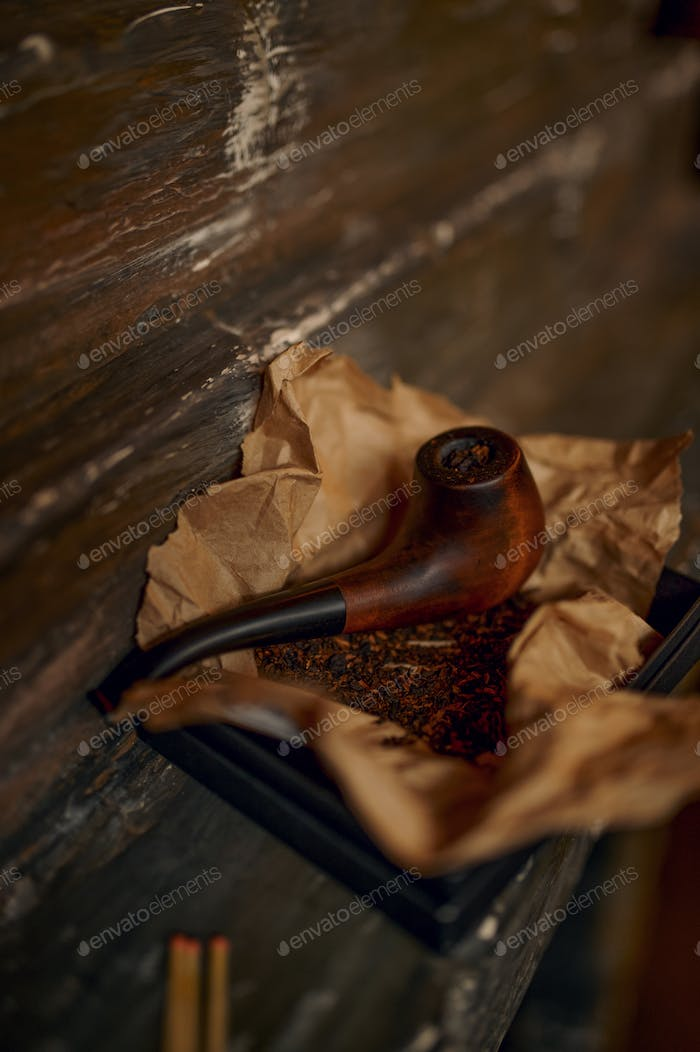 Smoking pipe and a pile of tobacco on wooden table