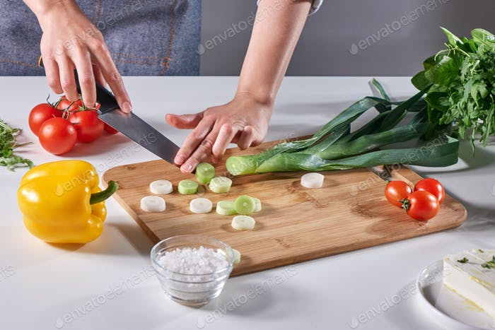 Woman's hands cut green leek on a wooden board on the kitchen table with various fresh