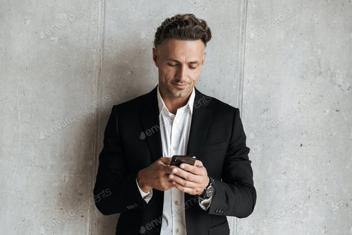 Handsome man dressed in suit holding mobile phone