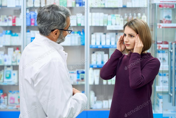 Pharmacist consulting woman with headache in drugstore