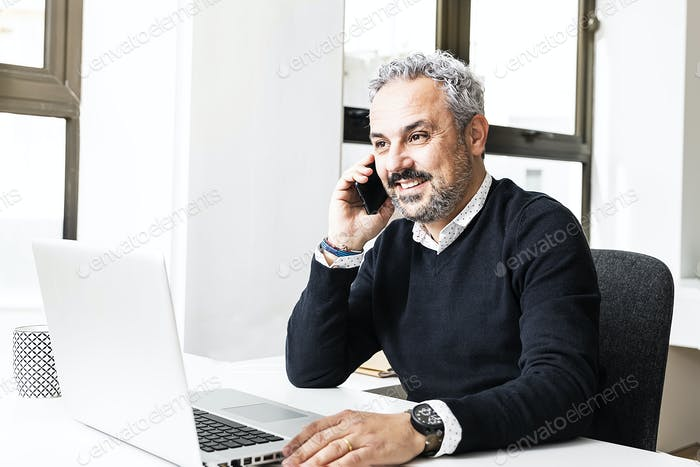 Senior businessman working on laptop computer talking on phone