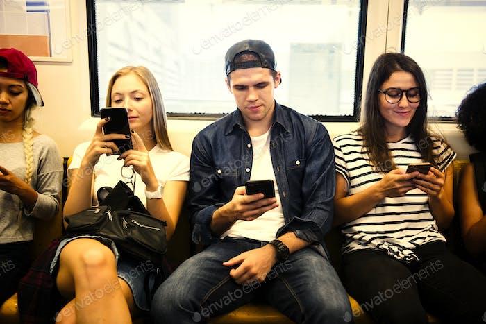 Gruppe von jungen erwachsenen Freunden mit Smartphones in der U-Bahn