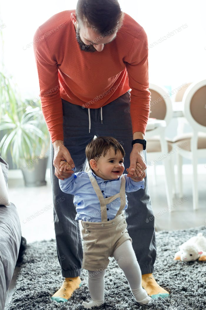 Handsome young father teaching to walking to his baby in living room at home.