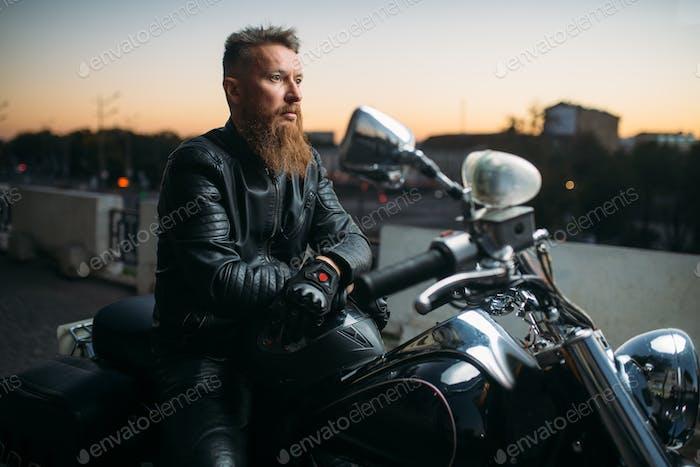 Biker posiert auf einem Motorrad in der Stadt auf Sonnenuntergang