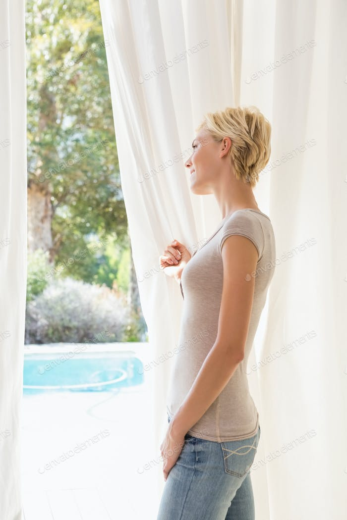 Hsppy blonde woman look outside at home