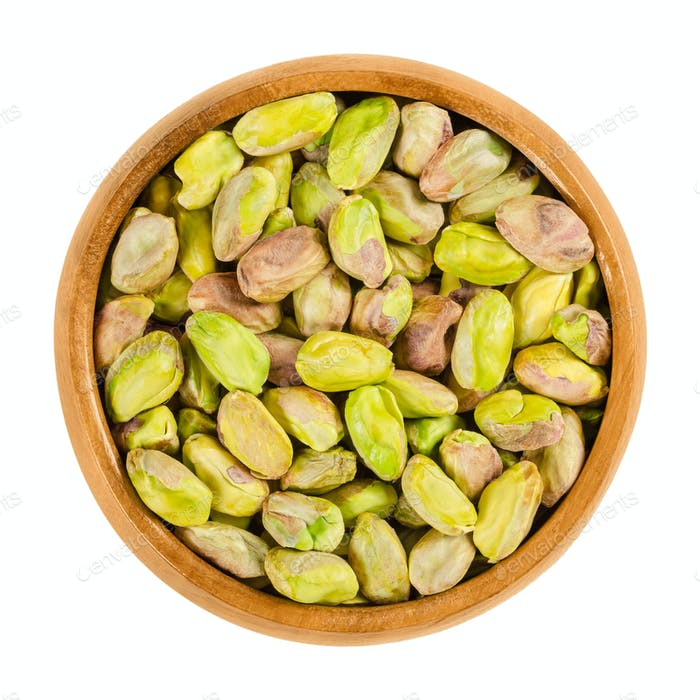 Shelled roasted pistachio kernels in wooden bowl over white