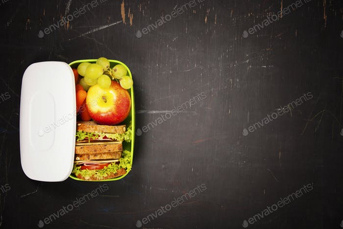 Green school lunch box with sandwich, apple, grape and carrot