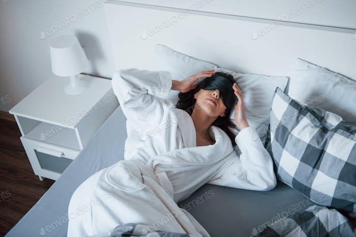 Woman with blindfold mask for a sleep is lying on the bed at morning time
