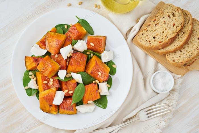 Salat mit geröstetem Kürbis, Feta-Käse, Spinat, Nüssen mit Honig und Gewürzen, Draufsicht