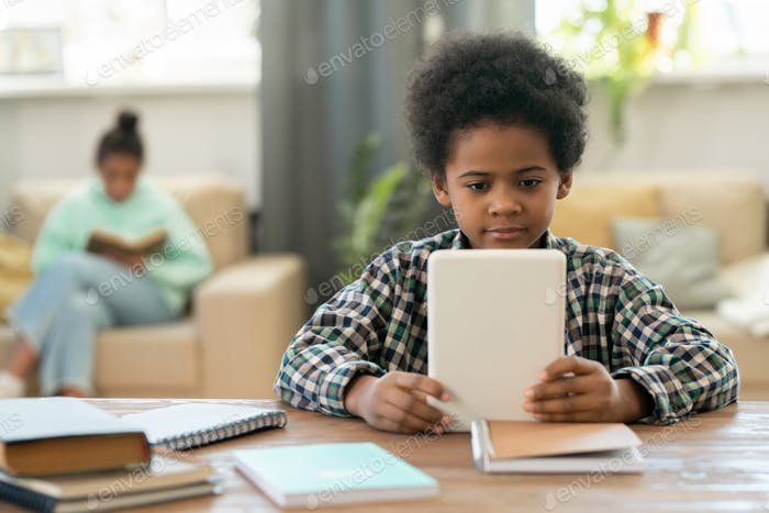 Cute elementary schoolboy of African ethnicity watching online lesson at home