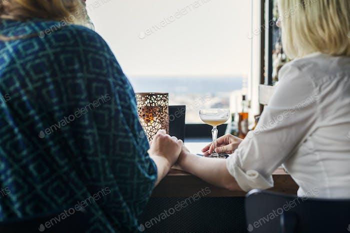Rückansicht des lesbischen Paares Hand im Restaurant