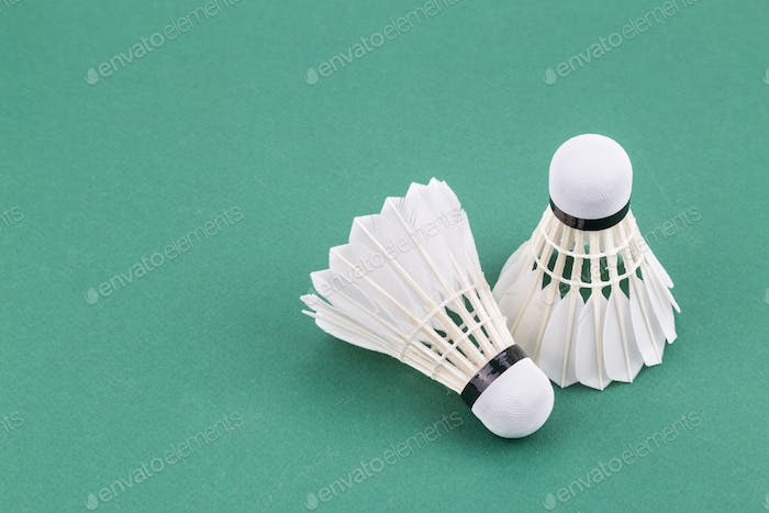 Two new badminton shuttlecock  on green court mat