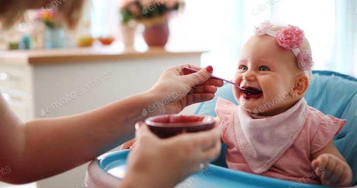 Mutter Fütterung Ihr Baby Mädchen mit einem Löffel