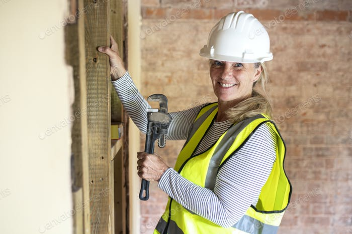 Woman worker remodeling home with a wrench