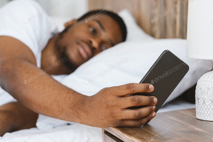 Black Man Turning Off Alarm-Clock Lying In Bed At Home