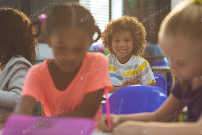 Schoolboy looking at camera while sitting at desk in school with school kids drawing
