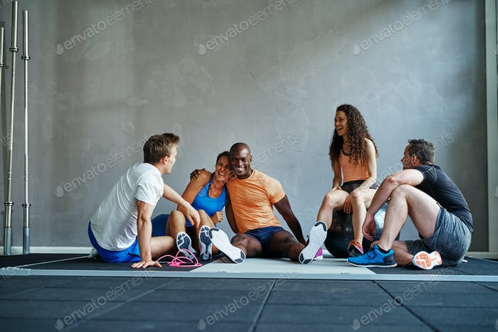 Friends talking and laughing together on a gym floor