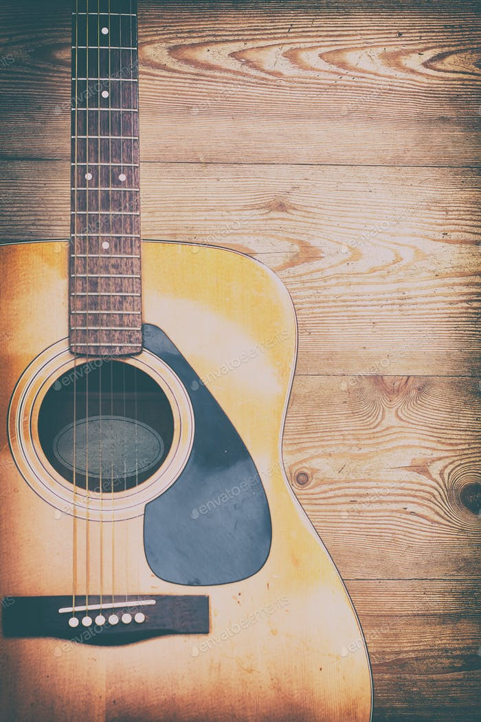 Acoustic guitar on rough wooden background