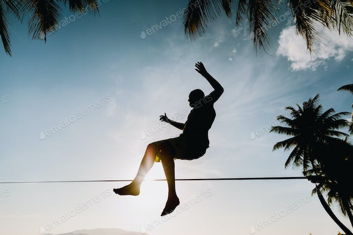 teenage jumping on slackline