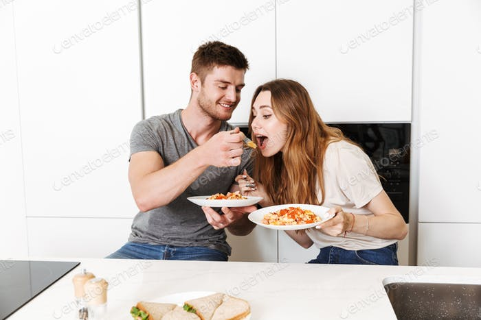 Smiling young couple eating breakfast together